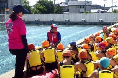 プールサイドでカヌーの説明を受ける子どもたち