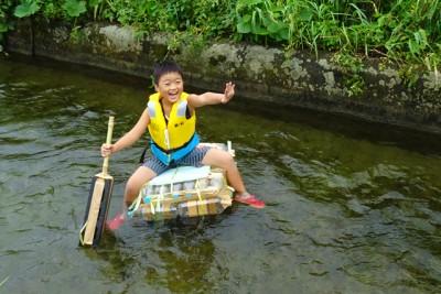 自作のいかだで川を下る男の子。楽しそうです
