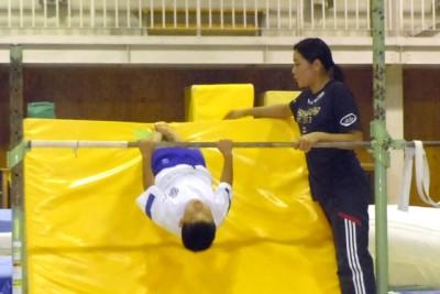 鉄棒の後ろに分厚いマットを壁のように置いて、逆上がりするのに足で登るようにして身体を持ち上げられるように補助