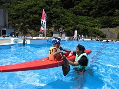 プールに浮かべたカヌーに乗った子供が指導員から教えてもらっています