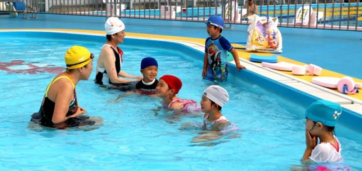 浅い幼児用プールで泳ぎを習う子供たち
