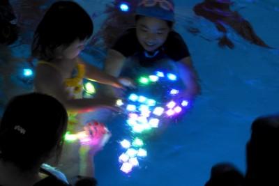 プールに浮かべたLEDライトを見つめる子供たち