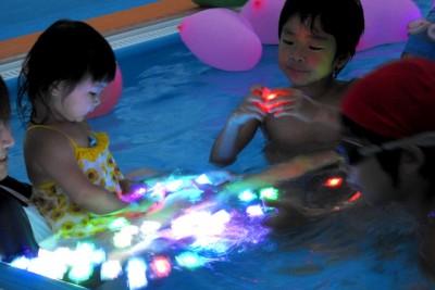 プールに浮かべたLEDを眺める女の子と手に取る男の子