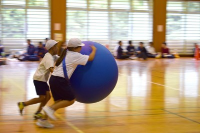 女の子と男の子の二人が大きなボールをもって疾走中!