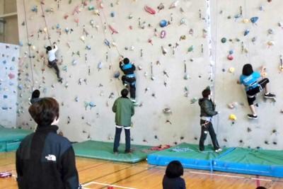 室内のクライミング用の壁をよじ登る子供たち