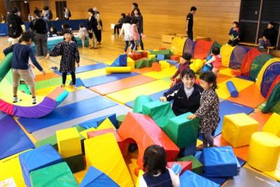 スポンジ状のいろんな形の立体のある遊具エリアで遊ぶ親子