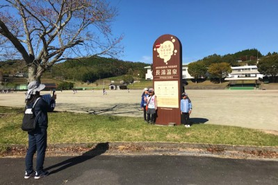 長湯温泉の看板と記念撮影をする参加者の方々