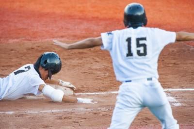ベースに向かってスライディングする選手