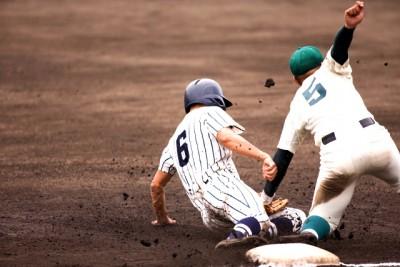 ベースに向かって走りこむ選手にタッチする野手