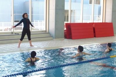 プールサイドの講師のポーズを、水中の参加者が真似て行います