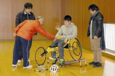 「障がい者スポーツを体験しよう」で競技用車イスに試乗している。講 師は徳島県障がい者スポーツ協会から