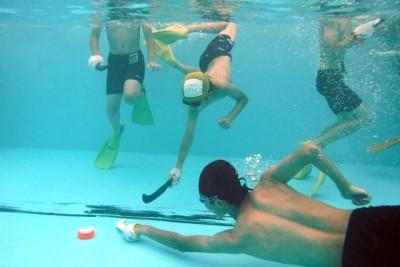 プールの底で、パック(的)のゴールインを競い合う水中ホッケー