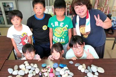 石ころアートに挑戦する未来のアーティストたち。作品を前に、指導して頂いた田中先生と一緒に「ピース!」