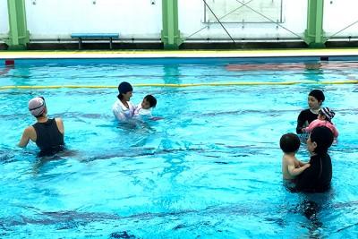 母親が子どもに笑顔で声を掛けながら、水中運動しています