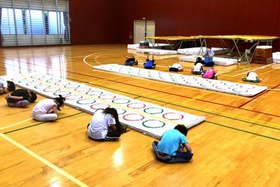 トランポリンを跳ぶ前に、みんなで柔軟体操やマット運動などで体をほぐします
