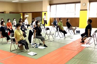 椅子に座りながらできる筋トレ。トレーナーの指導にみなさん真剣です